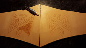 using a ceramic blade to carve the design into the leather